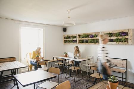 Zwei weibliche Erwachsene sitzen in einem Internet-Café und arbeiten mit einem Telefon und einem Laptop. Eine Kellnerin geht vorbei und zeigt Bewegungsunschärfe.