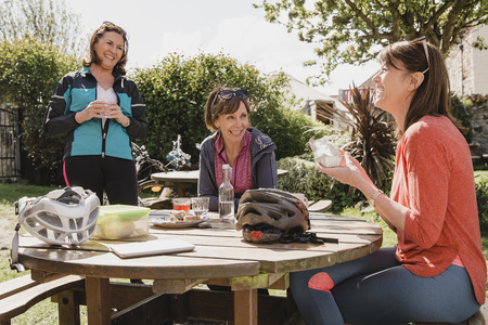 Small group of mature female cyclists sitting down in the outside seating area of a cafe. Tey are enjoying some refreshments as they take a break.