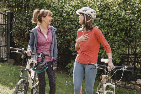 Two female friends walking into a public park with their bikes. They are looking at each other and talking as they walk in.