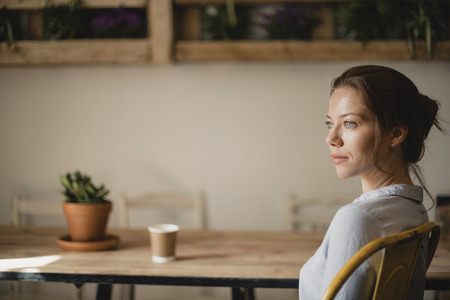 MId adult woman sitting at a take in a small cafe with a disposable coffee cup. She is looking out the window and enjoying the peace and quiet. Stock Photo