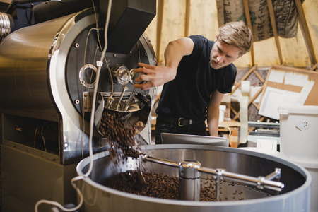 Male coffee shop employee using a coffee bean roasting machine and turning a dial to release the coffee beans. Reklamní fotografie