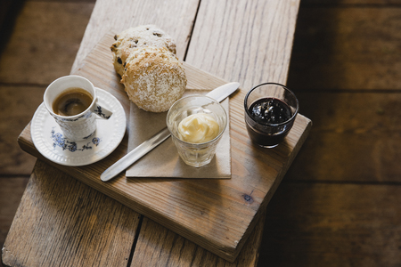 High angle view of a espresso coffee and scone on a wooden seat. There is some clotted cream and strawberry jam for the scone. Imagens