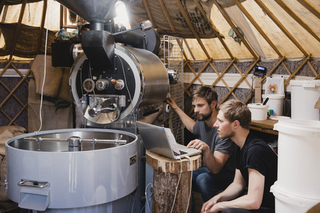 Two mid-adult men sitting in a room with a coffee bean roasting machine. They are looking at the laptop and fixing the machine, making sure it is working.