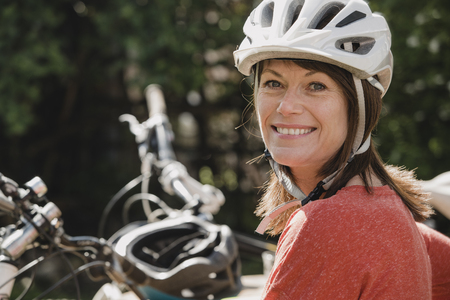 Headshot of a mature female wearing a cycling helmet and looking at the camera and smiling. Stock Photo