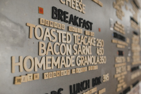 Low angle view of breakfast menu on the wall in a cafe. They have used little tile letters on the wall to spell out the different items on the menu.