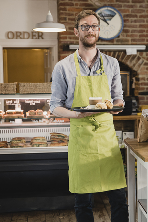 Portrait of a mid adult waiter in a coffee shop. he is looking at the camera and smiling while holding a tray with a coffee and scone on it. Imagens