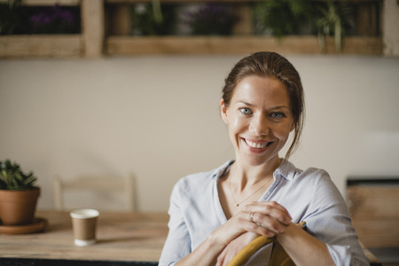 Headshot of a mid adult woman sitting indoors in a small coffee shop. She is looking at the camera and smiling.