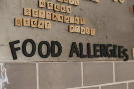 Low angle view of food allergies menu on the wall in a cafe. They have used little tile letters to show the words. Stok Fotoğraf