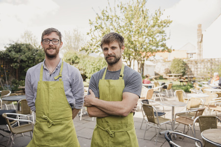 Portrait of two proud coffee shop owners standing infront of the outside seating area at their small cafe.