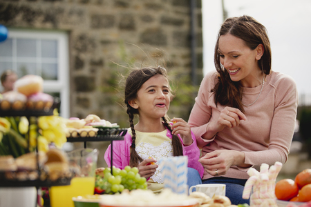 Young girl and her mother sitting outdoors during a garden party enjoying a picnic food.