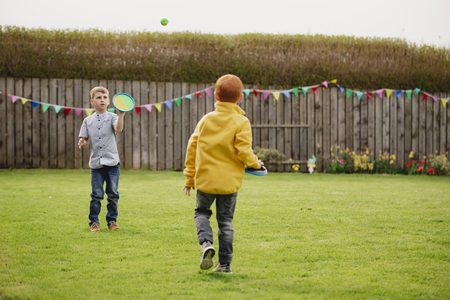 Two young boys playing outside in a back garden. They are throwing a tennis ball to each other and catching it with a velcro mitt. 写真素材