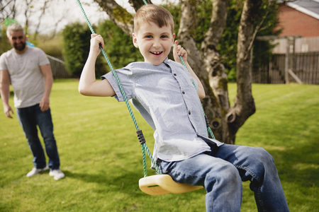 Young boy smiling while swinging on a swing outside. He is looking at the camera and having fun