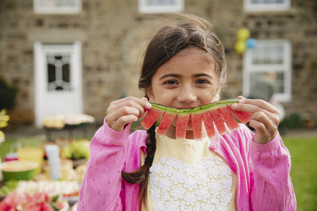One young girl looking at the camera while holding a slice of watermelon as a smile. Reklamní fotografie