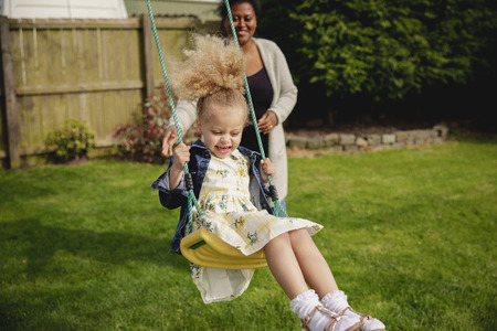 Little girl having fun while being pushed on a swing by her mother.
