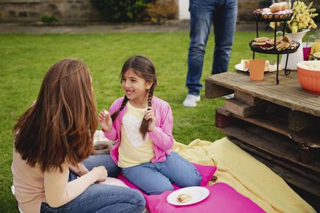 Little girl and her mother sitting outdoors on a blanket while talking. The little girl is talking and playing with her braided hair while at a garden party. Reklamní fotografie