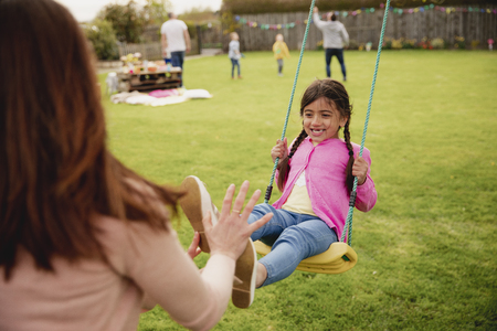 Little girl playing outside on a swing while her her mother helps and pushes her. She is having fun and enjoying herself.