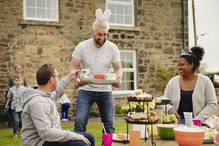 Mid adult man carrying a tray with cups of tea. He is handing out refreshments while wearing rabbit ears at a easter garden party.