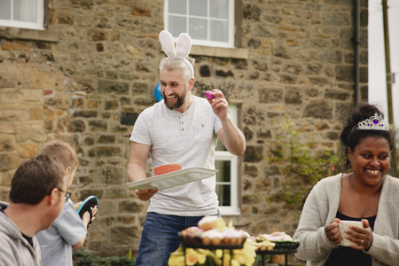 Mid adult man laughing and having fun with other parents at a garden party. He is wearing rabbit ears and holding a chocolate easter egg while smiling.