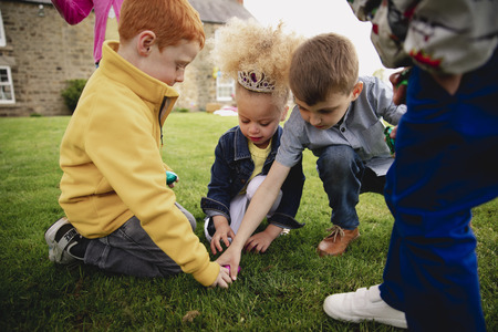 Group of young children kneeling down in a circle outdoors to share out the easter eggs that they have found.