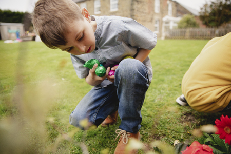 Young boy on an easter egg hunt with a friend. They are seaching for chocolate easter eggs in a back garden.