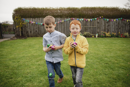 Two young boys walking through the back garden after an easter egg hunt. They are holding handfuls of chocolate eggs in their hands.