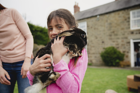 Young female child excited and happy to be holding a pet rabbit. She is smiling and looking at the camera.