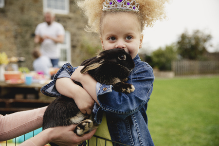 Little girl excited while stroking a pet rabbit ourdoors at a easter garden party.
