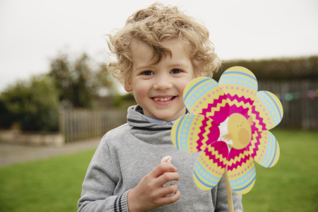 Little boy standning outdoors, looking at the camera while holding an easter egg themed windmill and smiling.