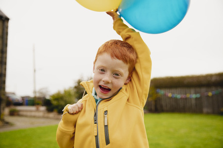 Headshot of a little boy looking at the camera while holding two yellow balloons and one blue balloon.