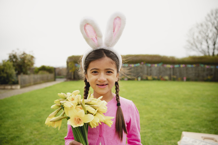 Portrait of a young girl standing outdoors while holding a bunch of daffodils and wearing rabbit ears.