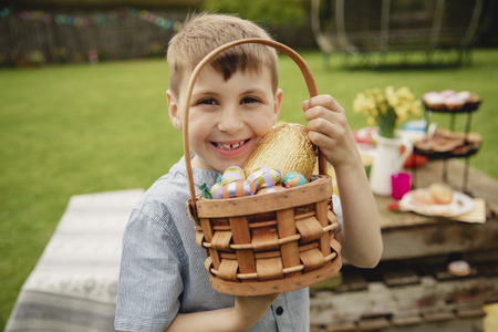 Young boy standing outdoors holding a basket full of chocolate easter eggs that he found on the easter egg hunt.