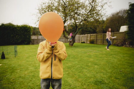 Creative headshot of a young unrecognisabe boy holding a balloon up to and covering his face.