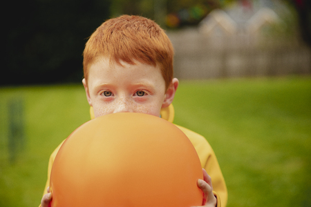 Little boy holding a orange balloon up to his face. He is looking at the camera and peering over the top of the balloon. Reklamní fotografie