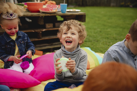 Excited little boy sitting outdoors with his friends surrounding him. He is amazed by the slime in a pot which he is holding.