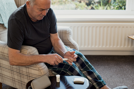Senior diabetic man is checking his blood glucose levels in the living room of his home.