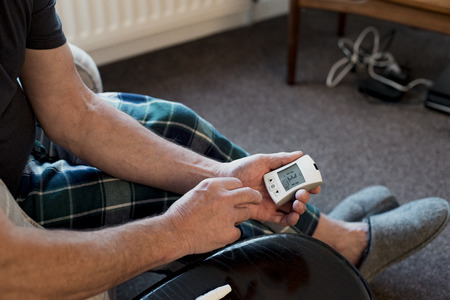 Close up shot of a senior man checking his blood glucose levels at home with a monitor. Reklamní fotografie