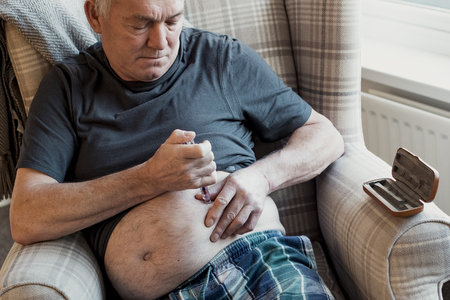 Senior man with diabetes is injecting insulin into his belly at home.
