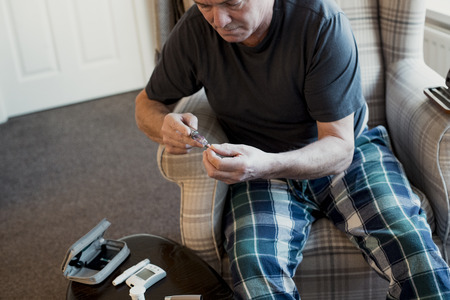 Senior diabetic man is preparing his insulin pen in the living rom of his home.