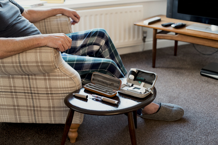 Senior man is relaxing in the living room of his home with a blood glucose testing kit on the table beside him. Stock fotó