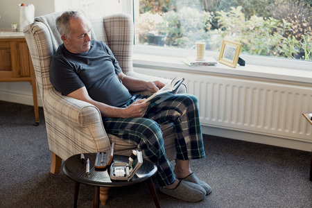 Senior diabetic man is relaxing in the living room of his home with a book. His blood glucose testing kit is on the table next to him.