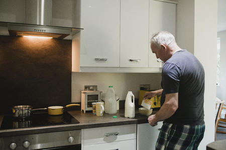 Senior man is making instant porrdige in the kitchen of his home.