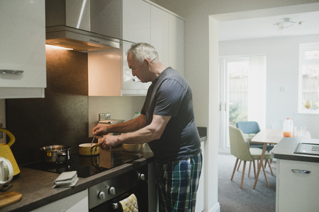 Senior man is preparing breakfast on the hob in the kitchen of his home.