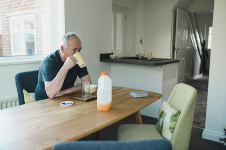 One senior man is sitting at the dining table in his home, enjoying porridge for breakfast with a cup of coffee and a glass of juice. Reklamní fotografie