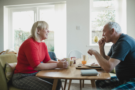Mature couple are having breakfast together at the dining table in their home.