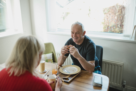 Senior man is laughing and talking with his partner while they enjoy breakfast together at home.