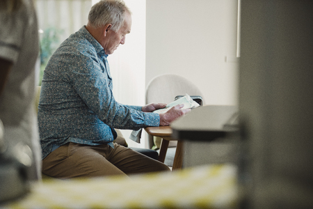 Senior diabetic man is sitting at a dining table reading a newspaper while his carer prepares his medication.