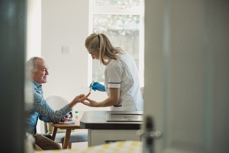 Senior diabetic man is having a check up at home from a district nurse. She is checking his blood glucose levels. Reklamní fotografie