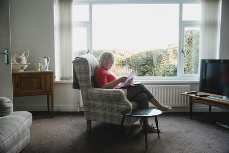 One mature woman is sitting in an armchair in the living room of her home, reading through letters. Reklamní fotografie