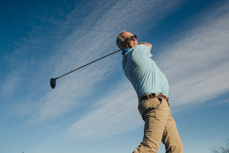 Ball perspective shot of a senior man swinging a golf club.
