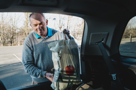 Senior man is placing shopping bags in the boot of his car. Reklamní fotografie